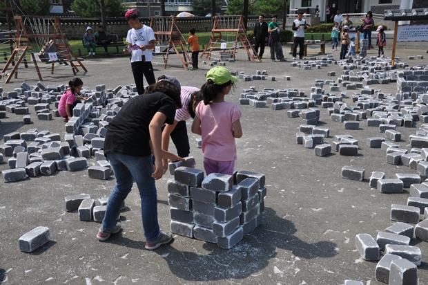 벽돌을 이용하여 벽을 쌓고 있는 모습