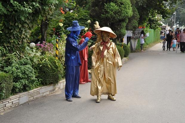 전통복장을 하고 전신을 한가지색으로 칠한 인간조각들의 모습