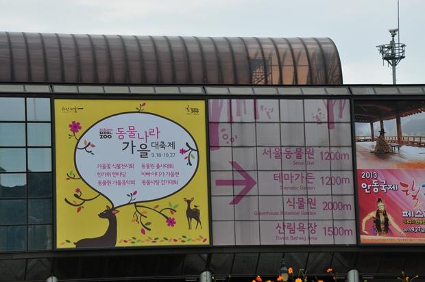 벽면에 위치한 동물나라 가을대축제 현수막과 그 옆에 이정표. 서울동물원 1200m 테마가든 1200m 식물원 2000m 산림욕장 1500m