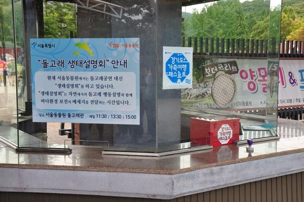 돌고래 생태설명회 안내 옆에 놓인 붉은색 경기도가족여행패스포트 상자와 도장