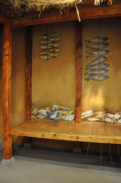 벽과 바닥에 물고기가 널어있는 벽화와 초가집 전시모형