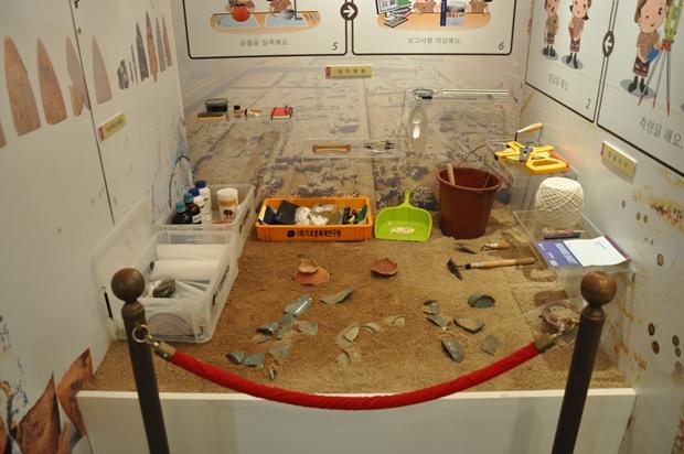 땅에 묻혀있는 유물을 발굴하는 모습을 전시해놓은 전시물