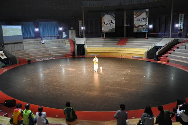 동그란 공연장 안에서 공연을 구경하는 사람들