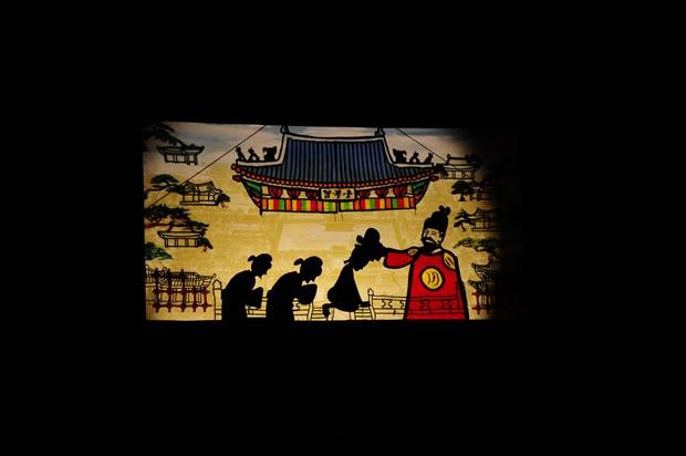어두운 조명 아래 스크린에 비추는 경복궁과 왕, 신하의 그림