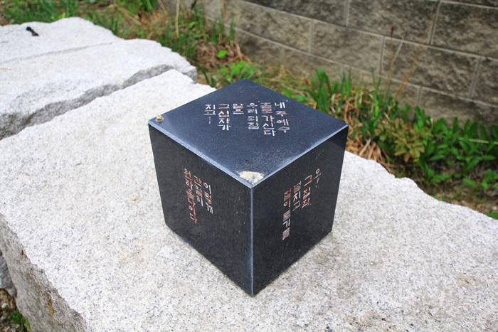 돌담 위에 올려져 있는 글귀가 적힌 작품