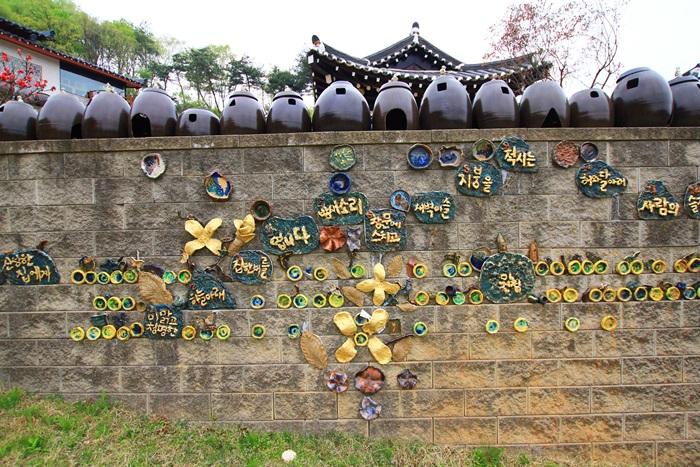 돌담장에 붙어있는 꽃모양과 글씨가 적힌 도자 작품들