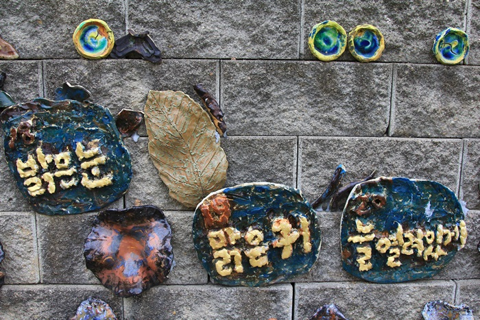 돌담에 붙어있는 밝은눈, 맑은귀, 늘열려있게 라고 적혀있는 작품들