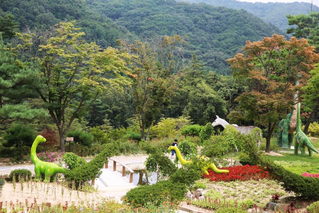 공룡 조각들이 있는 정원 모습