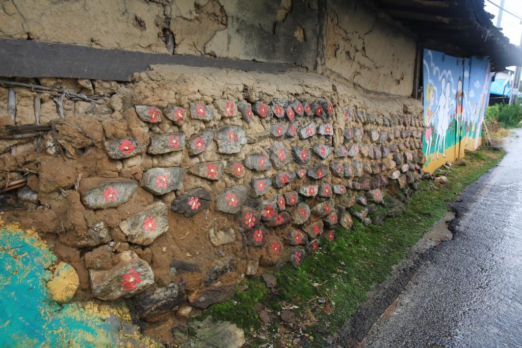 담벼락 돌 하나하나에 빨간색 꽃이 그려진 집