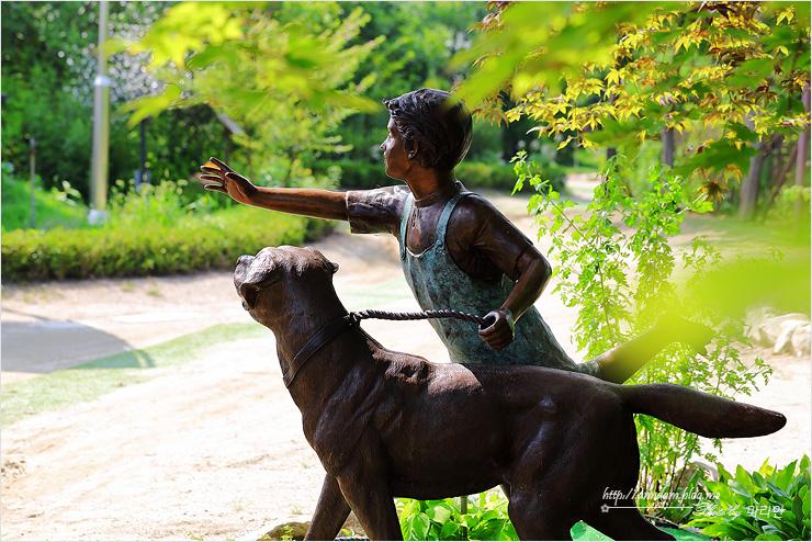 개와 산책하는 아이 동상