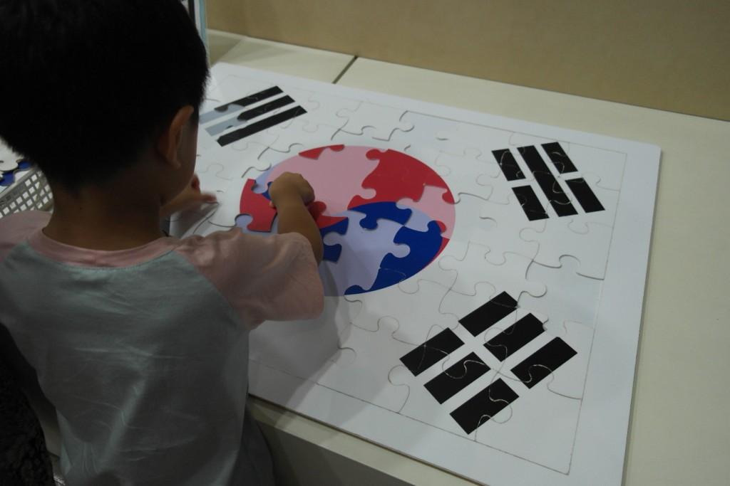 태극기 퍼즐을 맞추고 있는 아이