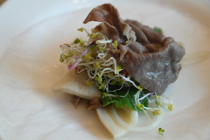 앞접시에 물에 적신 쌈종이를 깔고 고기와 각종 야채를 올린 모습