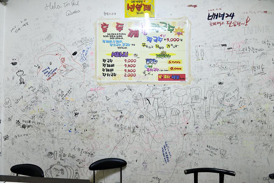 낙서로 가득한 벽면에 붙여진 차림표
