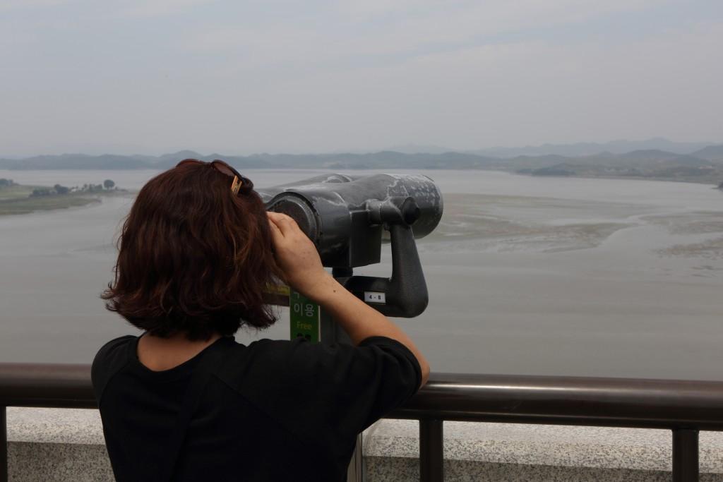 망원경을 보고 있는 여자의 뒷모습