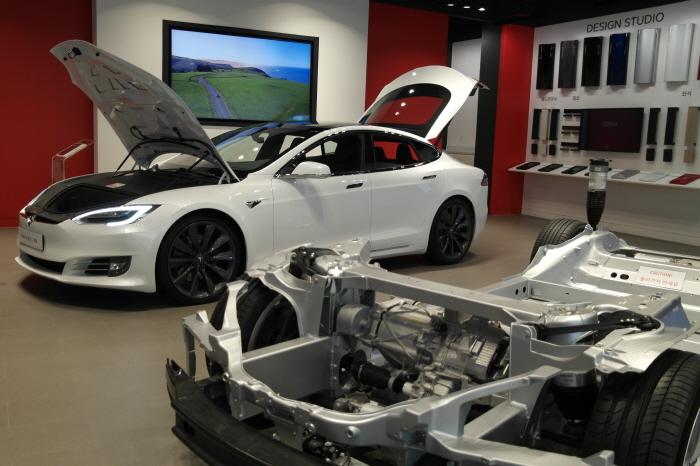 흰색 모델S 차량과 모델S의 샤시와 프레임이 노출