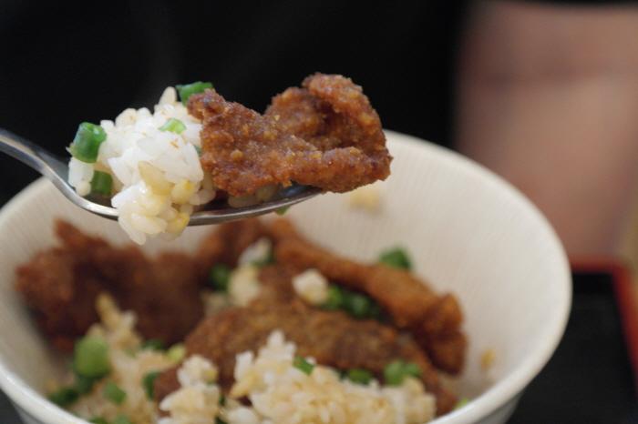조미한 보리밥 한숟가락에 올라간 고기 한점