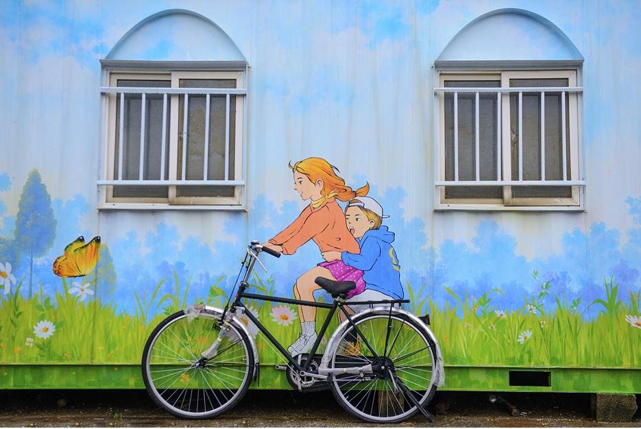세워진 자전거에 타고 있는 모습을 그려낸 벽화