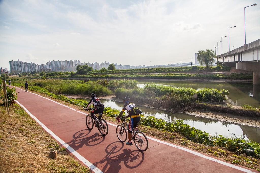 하천의 옆길로 자전거 타는 모습