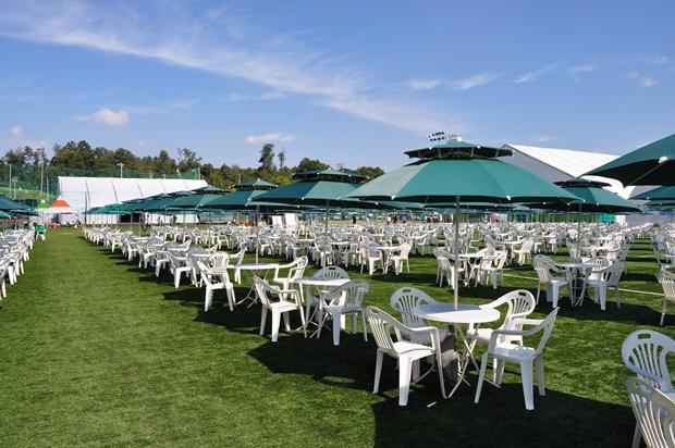 잔디 밭 위에 깔린 파라솔과 테이블들