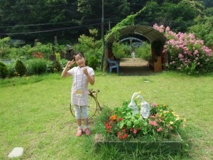 꽃이핀 정원에서 사진을 찍는 아이의 모습