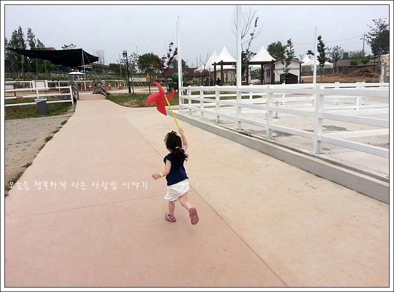 바람개비를 들고 뛰는 아이의 뒷모습