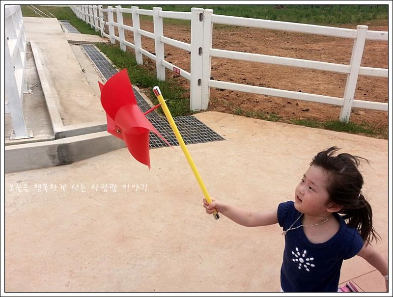 바람개비를 들고 뛰는 아이의 모습