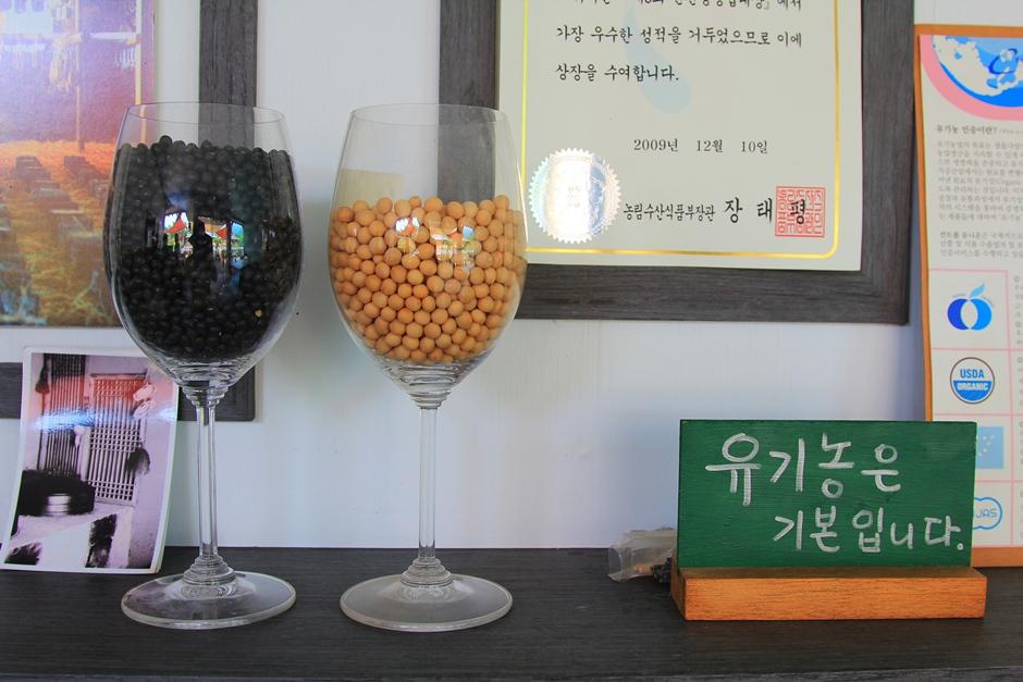 유기농은 기본입니다. 라고 쓰여진 작은 나무판과 와인잔에 들어간 콩들