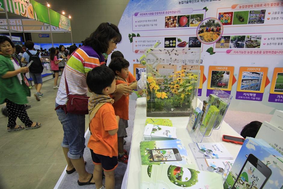 플라스틱 상자 속에 들어 있는 꽃을 관찰하는 아이들의 모습