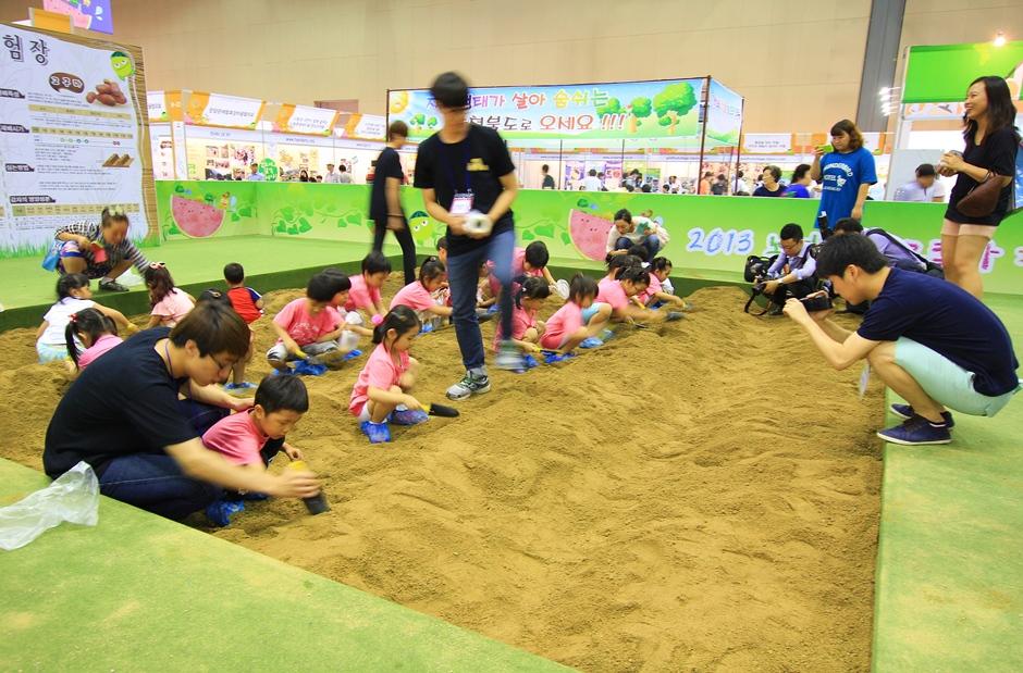 전시장 내 모래밭에서 무언가 체험을 하고 있는 아이들의 모습