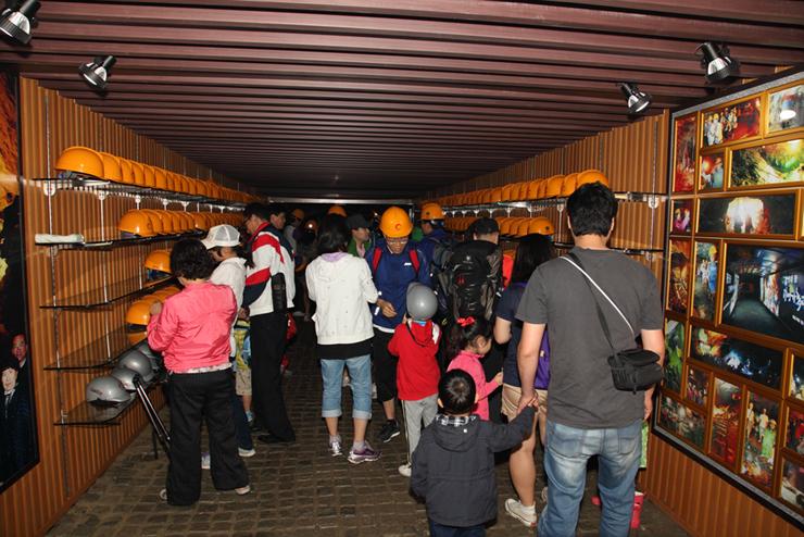 동굴 입구에 비치 된 안전모를 착용하는 사람들의 모습
