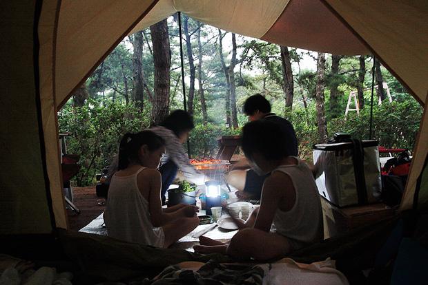 텐트 안에서 고기를 구워먹는 가족들