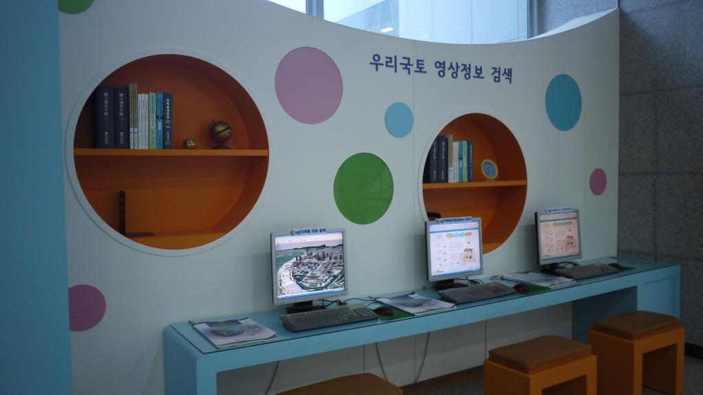우리국토 영상정보 검색이라고 쓰여져 있는 벽 앞으로 컴퓨터와 책이 비치되어 있다.