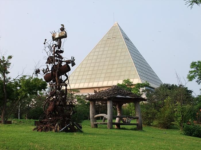 평택호예술관의 뾰족한 지붕과 그 앞의 야외조각공원에 설치되어 있는 작품의 모습