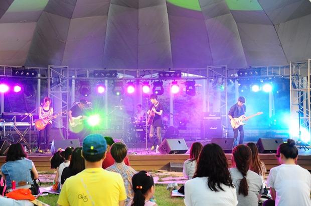 화려한 조명 아래서 공연하는 록밴드 몽키즈의 모습