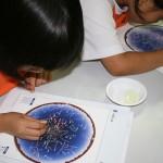 별자리가 새겨진 판으로 체험프로그램을 하고 있는 아이들