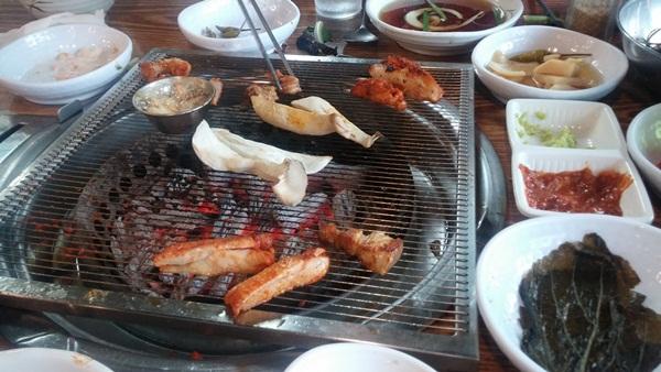 불판에 구워지는 고기와 버섯