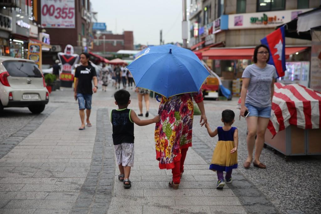 아이들과 손 잡고 걸어가는 외국인