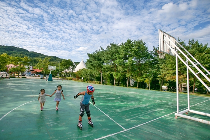 농구장에서 인라인스케이트를 타는 아이와 따라가는 아이들