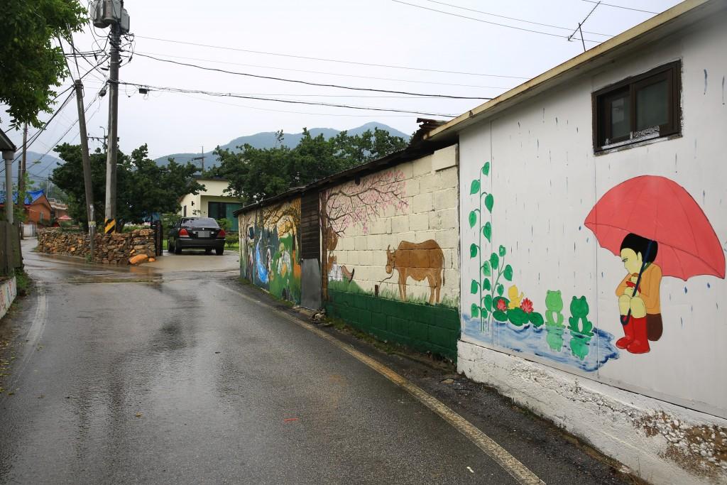 개구리를 바라보는 우산 쓴 소녀, 벚꽃 아래 소가 그려진 벽화가 있는 집