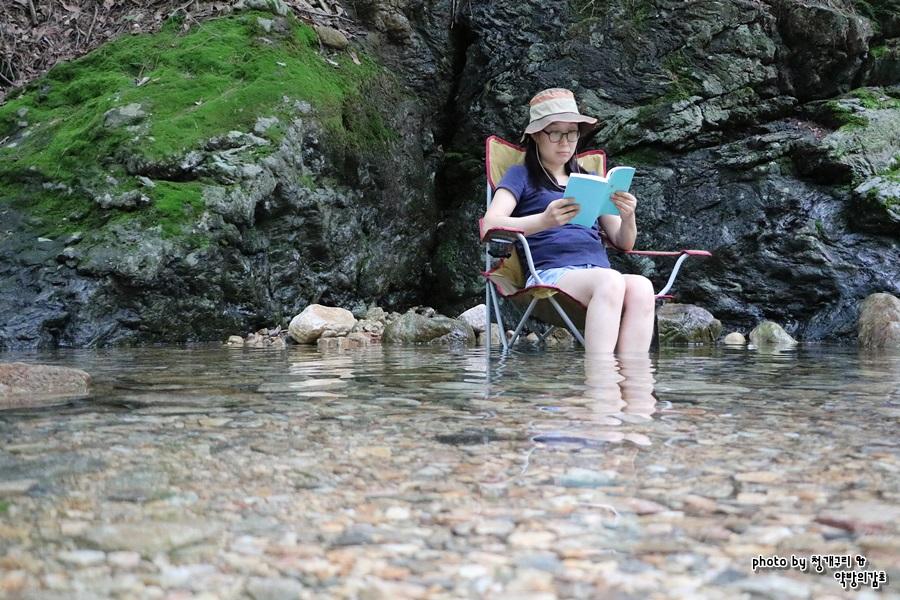 캠핑의자에 앉아 책 읽는 친구
