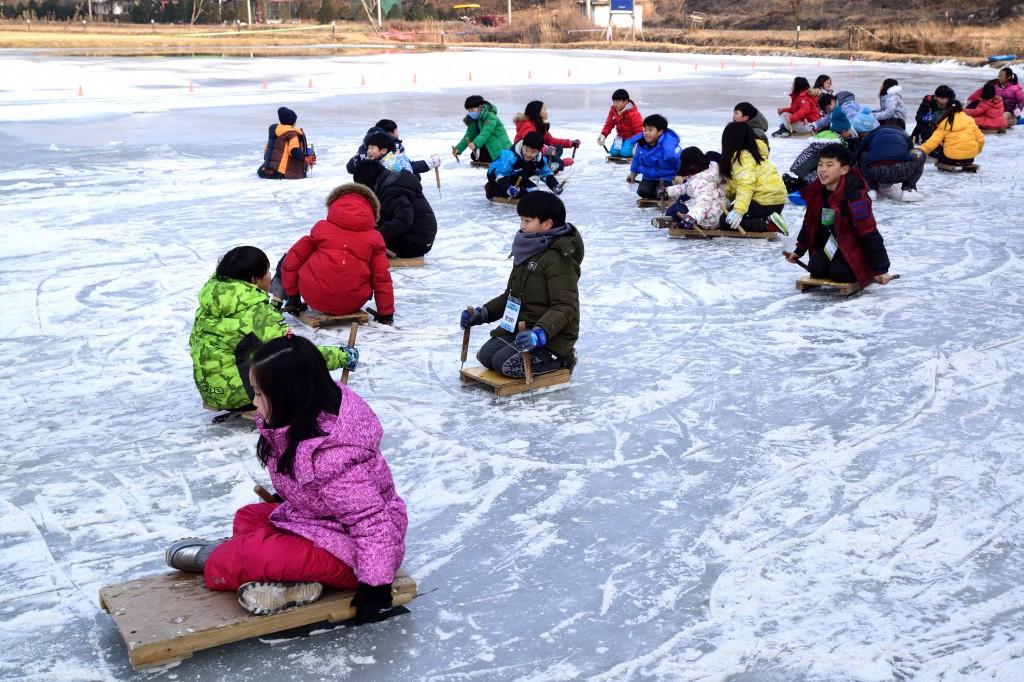 얼음판 위에서 썰매를 타는 아이들
