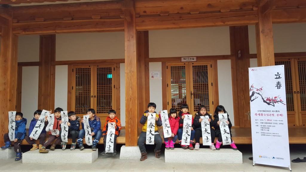수원전통문화관에서 입춘대길이라 쓰여진 종이를 든 아이들