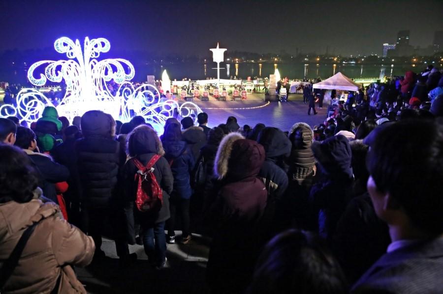 호숫가 앞 공연을 보는 사람들