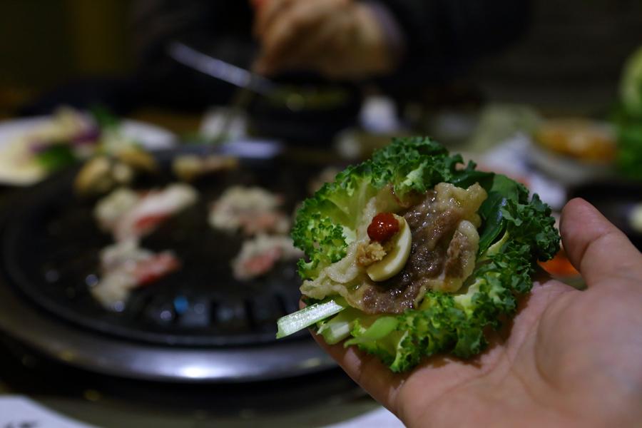 고기를 올린 쌈에 갈치 속젓을 넣은 모습