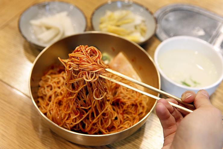 城南平壌冷麺の混ぜ冷麺を混ぜている。