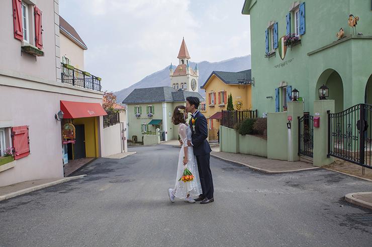 스위스 마을속에서 이마 입맞춤하는 신랑 신부