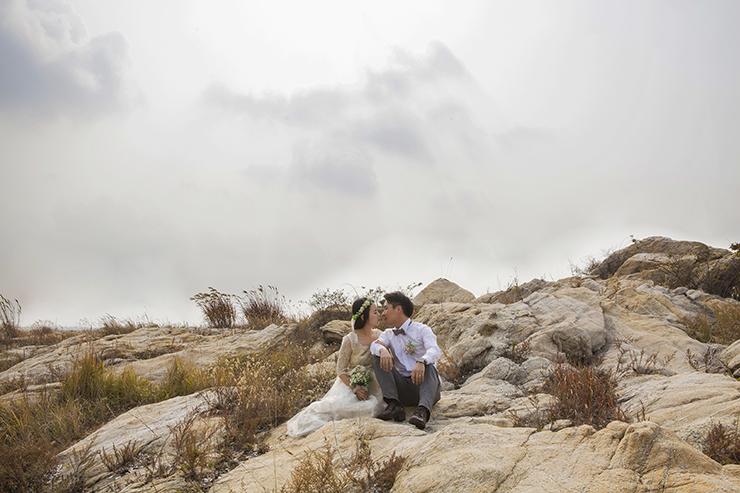 岩の上に座ってキスーのポーズをとっているカップル。