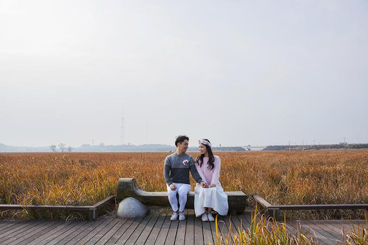 葦原のベンチに座ってポーズをとっているカップル。