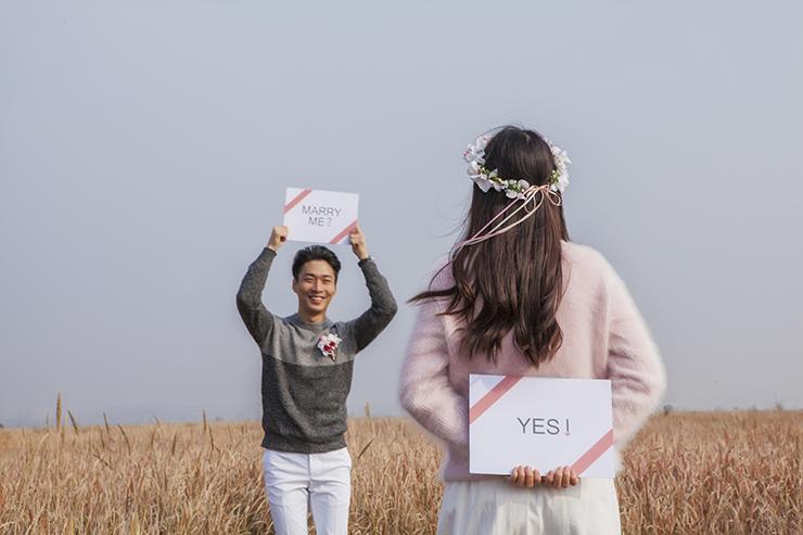 「Marry me?」、「Yes!」のピケットを持ってポーズをとっているカップル。