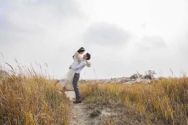葦原で花嫁を抱き上げている。
